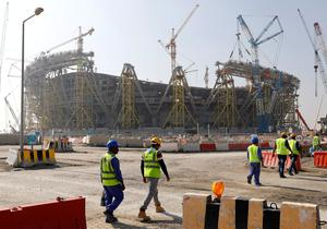 DOGGED: Workers walk towards Lusail World Cup stadium in Qatar. Pic: Reuters