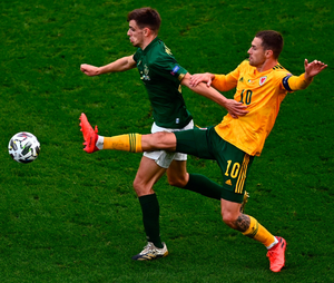The Republic of Ireland's Jayson Molumby holds off the challenge of Wales' Aaron Ramsey