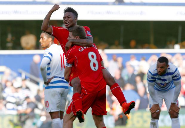 Liverpool's Raheem Sterling (REAR) celebrates with Steven Gerrard after his cross was deflected into the goal by Queens Park Rangers Steven Caulker