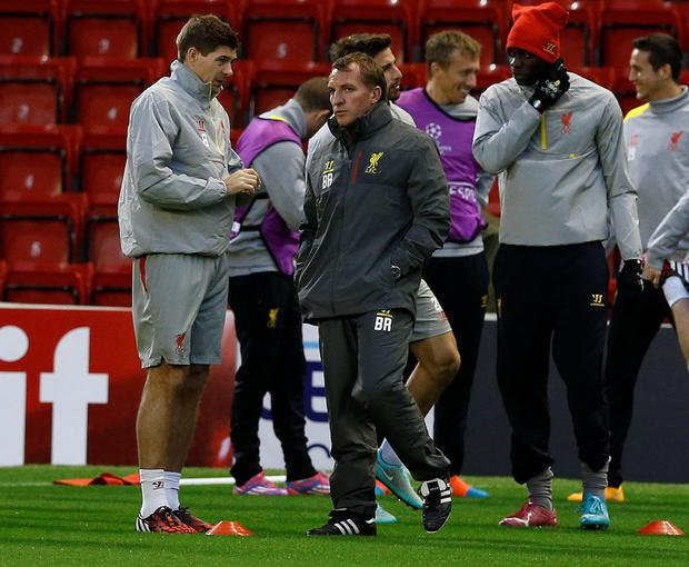 Liverpool's Steven Gerrard (L) talks with manager Brendan Rodgers (C) as Mario Balotelli (R) looks on during a training session at Anfield in Liverpool, northern England October 21, 2014.
