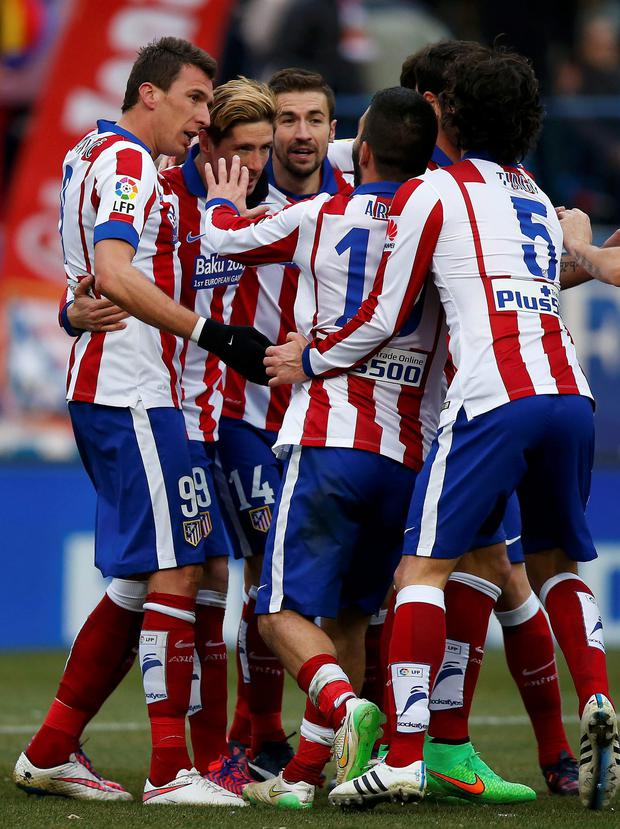 Atletico Madrid's Mario Mandzukic (L) celebrates with team-mates after scoring his team's fourth goal against Real Madrid during their Spanish first division soccer match at the Vicente Calderon stadium in Madrid
