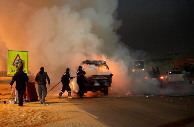 Egyptian firefighters extinguish fire from a vehicle outside a sports stadium in a Cairo's northeast district, on February 8, 2015 during clashes between supporters of Zamalek football club and security forces