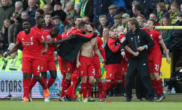 Adam Lallana celebrates with team mates and manager Jurgen Klopp after scoring the winning goal for Liverpool against Norwich on Saturday. Photo: Reuters