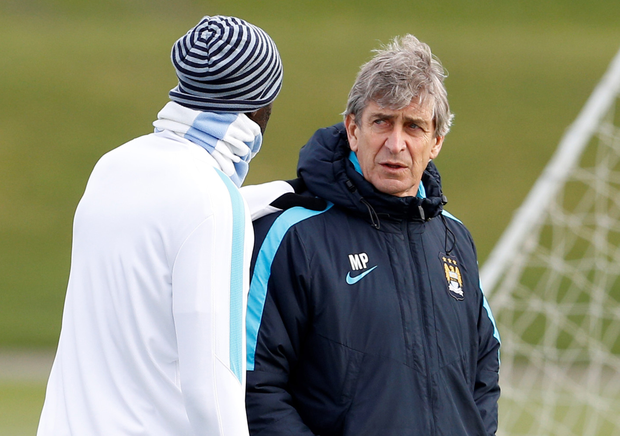 Manchester City boss Manuel Pellegrini chats with Yaya Toure in training ahead of tomorrow's League Cup final. Photo: Reuters