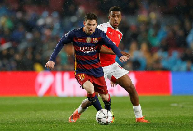 Barcelona's Lionel Messi keeps the ball away from Arsenal's Alex Iwobi