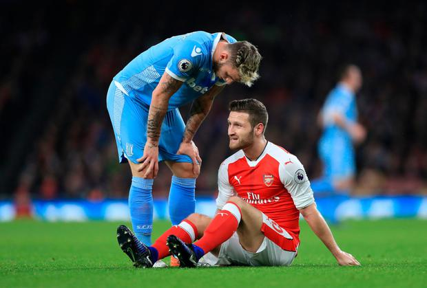 Arsenal's Shkodran Mustafi sits injured as Stoke City's Marko Arnautovic checks on his condition