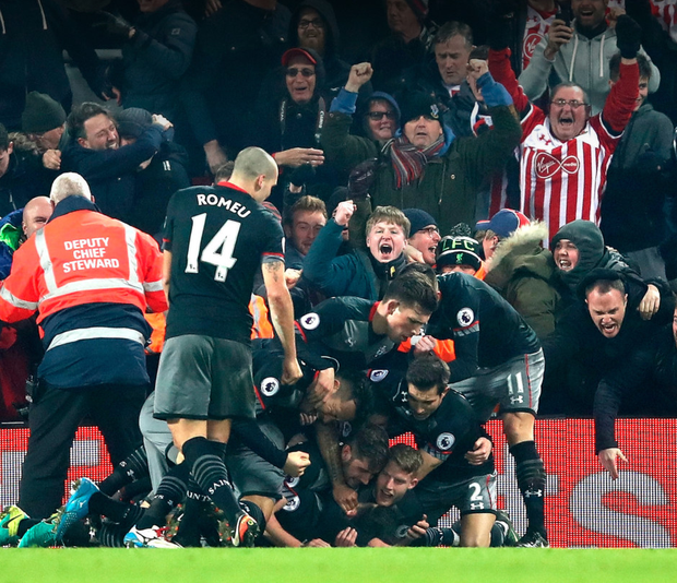 Southampton's Shane Long (bottom) is mobbed by his team-mates after scoring his side's first goal during the League Cup semi-final second leg match at Anfield. Photo: Getty Images
