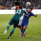 Pedro (r) is tackled by Arsenal goalkeeper David Ospina in Saturday's friendly match in Beijing. Photo: Reuters