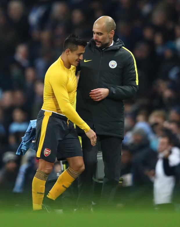 Arsenal's Alexis Sanchez and Manchester City manager Pep Guardiola embrace after their Premier League match at the Etihad Stadium in December last year. Pic: Getty Images