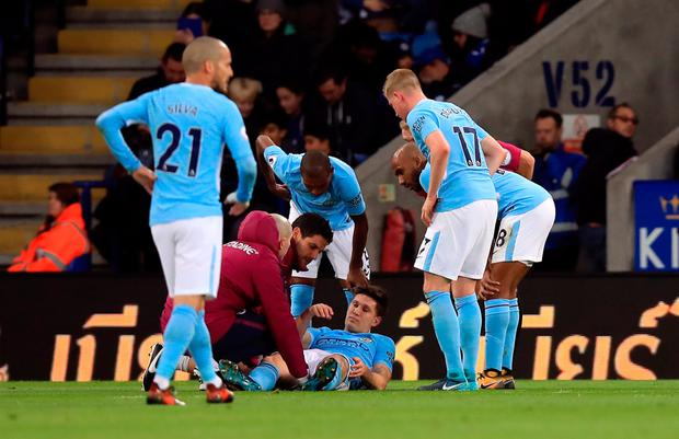 Man City players crowd around the injured John Stones. Photo: PA