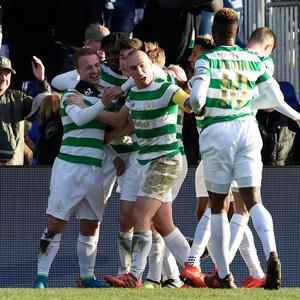 Leigh Griffiths (l) is swamped by his Celtic team-mates after scoring. Photo: PA