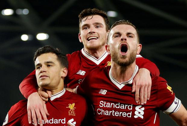 (l-r) Philippe Coutinho, Andrew Robertson and Jordan Henderson celebrate in Saturday's win at Brighton