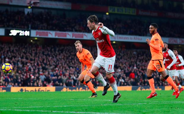 Mesut Ozil chips home Arsenal's third goal in last night's Premier League draw with Liverpool. Pic: Getty