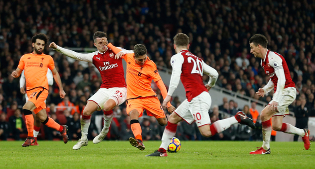 Liverpool's Brazilian midfielder Roberto Firmino (c) scores his team's third goal during the Premier League draw with Arsenal at the Emirates Stadium. Pic: Getty