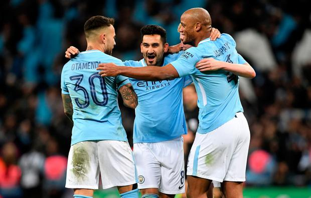 CUP OF CHEERS: Ilkay Gundogan (c) celebrates Sunday's League Cup win with Nicolas Otamendi and Vincent Kompany. Pic: PA