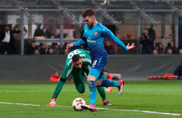 Arsenal's Aaron Ramsey rounds AC Milan goalkeeper Gianluigi Donnarumma to score during the Europa last-16 win over AC Milan