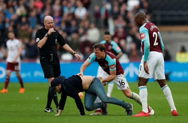 FAN-GRY: West Ham United's Mark Noble clashes with a fan who has invaded the pitch during Saturday's defeat to Burnley at the London Stadium. REUTERS