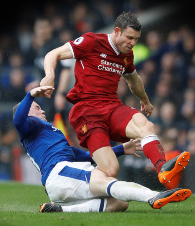DERBY TUSSLE: Liverpool's James Milner ships a sliding tackle from Everton's Wayne Rooney during last Saturday's drawn Merseyside derby at Goodison Park.