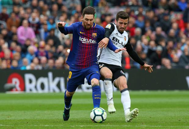TIGHT SPOT: Barcelona's Lionel Messi in action against Valencia's Jose Luis Gaya Photo: Reuters