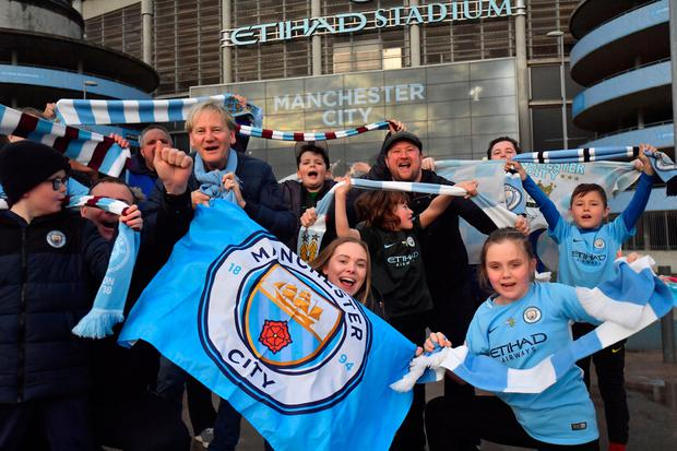 Manchester City fans with flags celebrate as Manchester City win the premier league (PA)