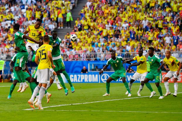 Colombia's defender Yerry Mina (C) heads and scores a goal