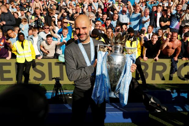 Manchester City manager Pep Guardiola lifts the Premier League trophy at the Amex Stadium last Sunday