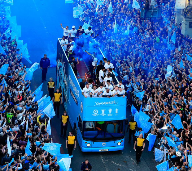 The Manchester City players and staff on the buses pass the crowds of fans gathered on the route during the trophy parade in Manchester