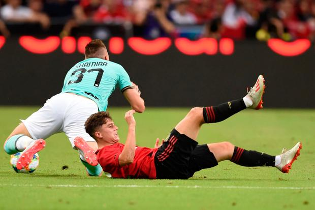 Inter Milan's Milan Skriniar (l) falls to the ground beside Manchester United's Daniel James