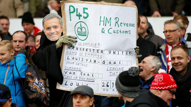 A Stoke fan wearing a Jose Mourinho mask and dressed as the Grim Reaper poses with a P45 banner for Manchester United manager Louis Van Gaal on Saturday Photo:Reuters