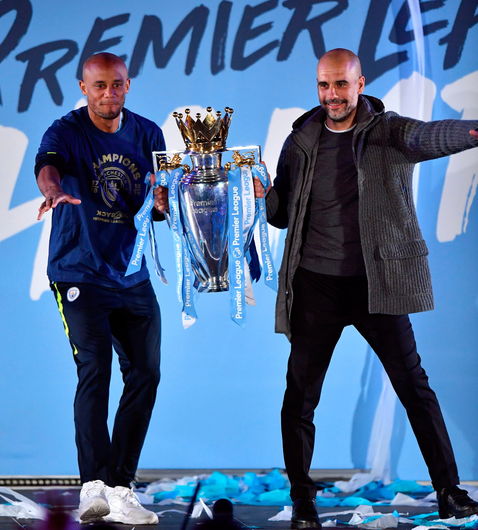 Manchester City's Vincent Kompany and manager Pep Guardiola on stage with the trophy during the celebrations at the Etihad Stadium after securing the Premier League title. Photo: PA