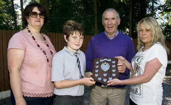 Seosamh Mac a'tSithigh receives the Jessica de Priondaibhéil Memorial Shield for 'The best overall Effort' from the late Jessica's mom, Marie Keane and guest of honour, Weeshie Fogarty in the presence of Seosamh's proud mom, Marie Sheehy at the Gaelscoil Aogán Graduation Awards on Tuesday. Photo by John Reidy
