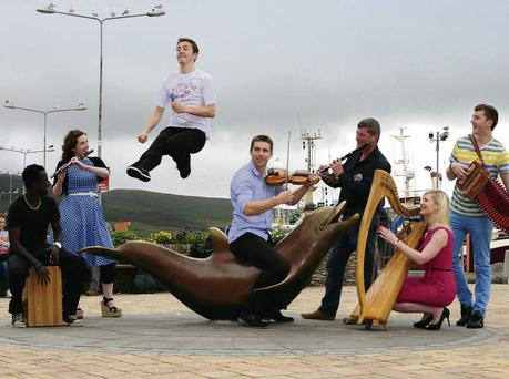 World Dancing champion David Geaney soars over Fungie's statue as Kerry footballer Marc O'Se joins musicians Aoife Granville, Darran Roche and Patrick Hazelton, from MOXI, and Christine McGrattan and Jerry O'Sullivan to launch this year's Dingle Tradfest.