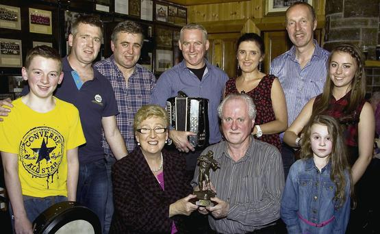 Maureen Murphy receiving the Patrick O'Keeffe Traditional Music Festival Award for dedication to the Music of Sliabh Luachra from Matt Cranitch. Also included are Eoin, Kevin, Seán, Dónal and Eibhlís Murphy, Cormac O'Mahony, festival chairman, Melanie and Caoimhe Murph at Fagin's Bar.