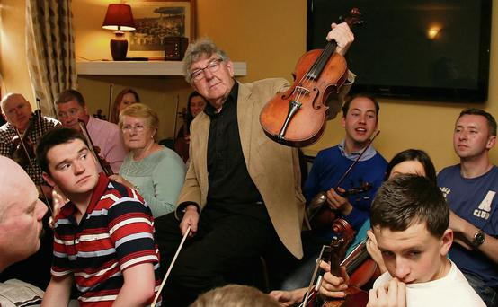 Master of Ceremonies, Nicky McAuliffe holding up the fiddle which belonged to Patrick O'Keeffe at Lyons' Bar during the World Fiddle Day celebrations in Scartaglin on Saturday afternoon.