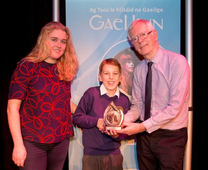 Ben Mac Eoin being presented with the Junior Solo Contemporary Music Performance title by Seán Ó Ceallaigh, National Schemes Manager, Gael Linn and adjudicator Edel Ní Churraoin at the Scléip All-Ireland held in Clontarf on Thursday