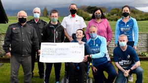 Micky Fleming Order of Malta Ambulance Killarney Division (left) receiving a cheque for €2030 from Ronan and Tony Foley, Killorglin, the proceeds of the Virtual Dublin City Marathon by Tony Fleming, Ciaran Ó Muircheartaigh and Catherine Doyle. Also in photo (front right) Ciaran O'Muircheartaigh, (back from left) Donal McCarthy, Order of Malta, James Doyle, Ian Holohan, Order of Malta, Caroline Foley and Catherine Doyle in Killorglin. Photo by Michelle Cooper Galvin