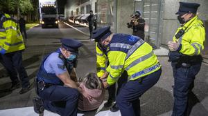 Gardaí remove a protesting former worker from the roadway to allow agents of Debenhams' liquidators KPMG remove stock from the retail chain's former outlet at Manor West in Tralee in the early hours of Saturday, April 24. Photo by Domnick Walsh