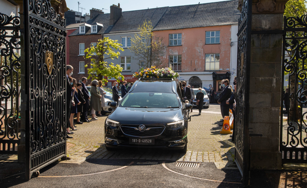 A socially distant guard of honour looks on as the remains of the late Joe Revington SC arrive at St John's Church on Ashe Street for his funeral service on Monday. Photo by Joe Hanley