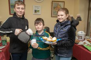 Killian Boyle pours a cuppa tea for James Harrington and Audrey Ryan at the Bud Family Resource Centre charity coffee morning to help raise funds for the charity, 'SOFT'.