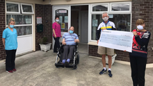 Michael O'Callaghan presenting the proceeds of his own personal Ring of Kerry challenge this year by way of a cheque for €800 towards vital PPE gear. Also pictured with Michael and staff of Árus Mhuire is Michael's brother-in-law Anthony, a resident of the Listowel centre on whose bedroom wall now proudly hangs the big cheque
