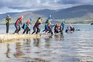 Young swimmers leap into the water at Fenit under the watchful eye of coach John Edwards. Photos by Domnick Walsh