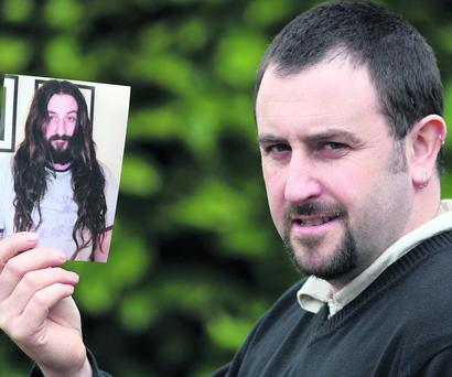 Brendan McKenna holding a photograph of himself as he looked before his charity headshave. Photo: John Reidy