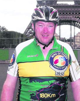 Tommy Sheehy at the Eiffel Tower, Paris after riding from Dublin for Enable Ireland in 2011.