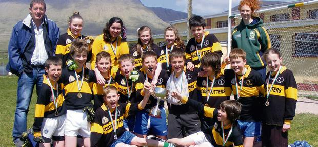 The team from Gaelscoil Aogáin, Castleisland, Co. Kerry celebrating with school principal and trainer, Tomás Ó Conchúir, and Louise Ní Mhuircheartaigh, member of the Kerry Senior Ladies Football team, following their win at the Gael Linn Féile Peile 2013 in Lispole recently.