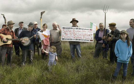 Little Aoibheann O'Leary from Bunagarha, Listowel, waves a tricolour as local musicians and protestors gather around a banner proclaiming 'Save rural Ireland, No to EU Dictatorship' at a rally on Moanveanlagh bog near Listowel on Sunday.
