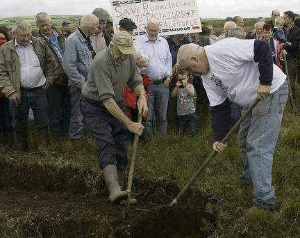 Michael D O'Sullivan and Mick Scannell make a symbolic gesture by cutting turf with a slean at a protest on Monveanlagh bog. Photo by Ann McNamee