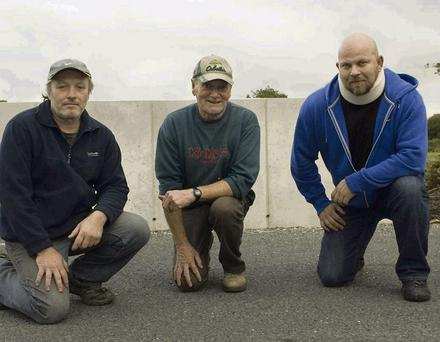 Tony Uljee, Sean Roche and Brian Finucane at the recently repaired stretch of road at Gortnacoca Bridge, Ballylongford, which, they claim, needs more work. Photo Ann McNamee