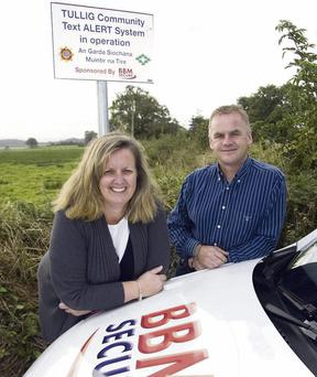 Tullig Community Alert committee member, Noreen O'Sullivan pictured with Paudie Barrett of BBM Secure and one of the in the area signs which Mr Barrett's company sponsored.