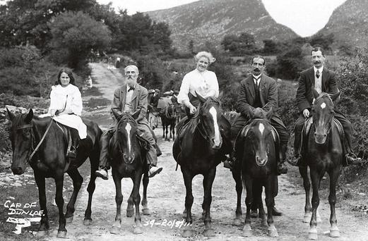 A young girl rides astride a pony beside the local guide in the company of a lady riding side saddle, and two gentlemen at the Gap of Dunloe, 1911. Following behind is a group in a jaunting car while in the distance a woman in a white blouse tends geese.