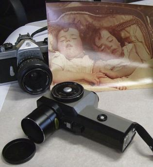 Some of the Greasai's camera equipment and the photograph of his sleeping children that won a major international award.